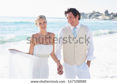Newlyweds walking hand in hand and smiling at the beach