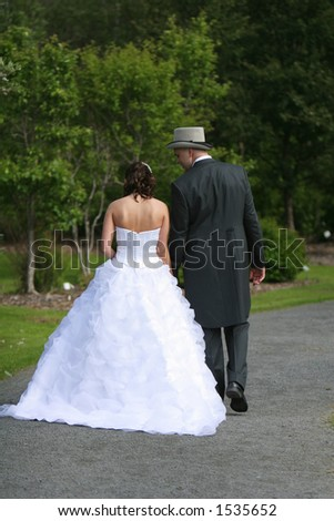 Newlyweds walking through a botanic garden after the ceremony enjoying a quiet moment alone together before the reception