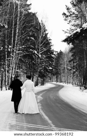 Newlyweds walks away outdoors. Road in the forest