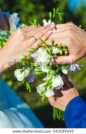 newlyweds with a bouquet of irises by sunny day outdoors #543589642