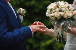 newlyweds with rings on fingers at wedding day. wedding ceremony. couple exchanges the gold wedding rings close up. happy just married couple. she put wedding ring for him. bride put ring for groom.