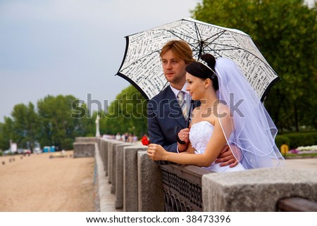 newlyweds with umbrella lean one's elbows on handrail