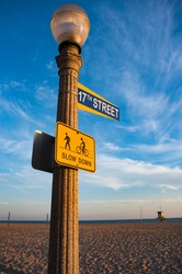 Newport beach 17th street sign on lamp post with pedestrians and cycle path sign