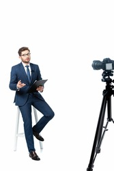 news commentator with clipboard sitting on high stool near digital camera on white, blurred foreground