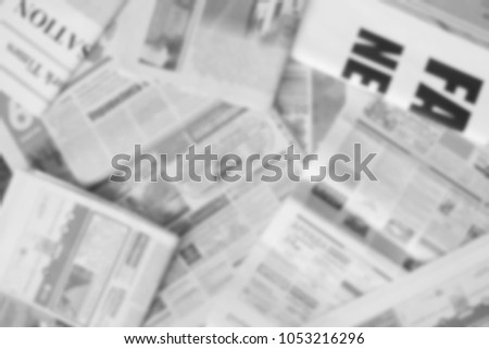 News concept - newspapers scattered on horizontal surface, top view. Daily papers with headlines and articles, blurred background texture #1053216296
