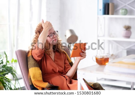 News on tablet. Sick woman reading news on tablet and drinking tea while having flu and fever