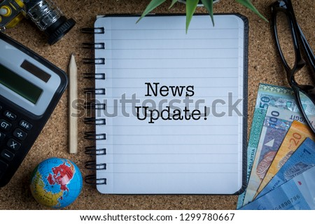 NEWS UPDATE inscription written on book with globe,eyeglasses, calculator, camera, pencil and vase on wooden background with selective focus and crop fragment. Business and education concept Stock fotó ©