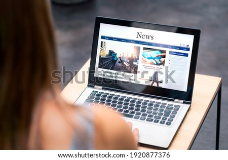 News website in laptop screen with online article and headline. Woman reading newspaper or magazine with computer. Digital web publication portal and internet page. Latest daily media site mockup. Сток-фото ©