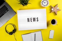 News word on lightbox on modern yellow office desktop with laptop, smartphone, coffee mug, notebook. world imbued with information, informational reasons, daily news, messages, informational noise