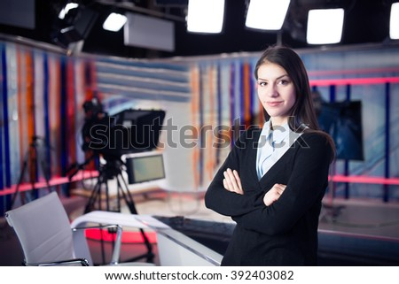 News writing and reporting.Woman journalist in television studio standing with her arms crossed.Determination,journalistic fairness and accuracy.Interview talk show with live audience.Media industry