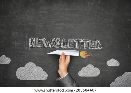 Newsletter concept on black blackboard with businessman hand holding paper plane