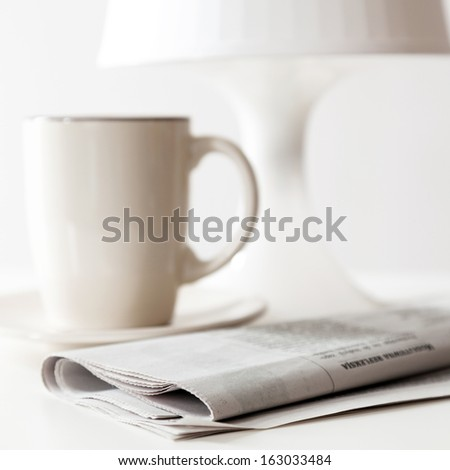 Newspaper and a coffee cup on a white table #163033484