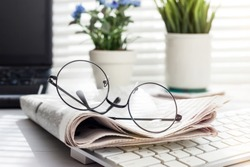 newspaper and glasses over office desk