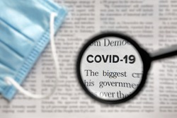 Newspaper Article with the Headline Covid 19. News about Coronavirus Pandemic on a newspaper through a magnifying glass. News Related to the corona virus. Medical mask. Face Mask. News media Concept