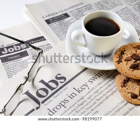 Newspaper classifieds and coffee cup with cookies