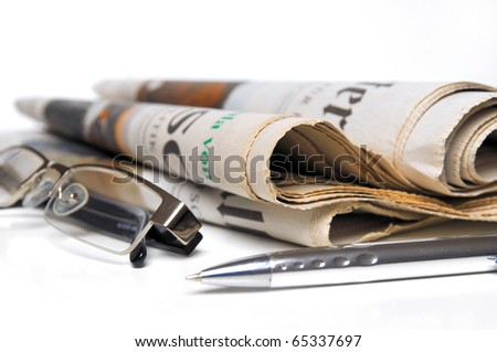 Newspaper,glasses and ball point over white background