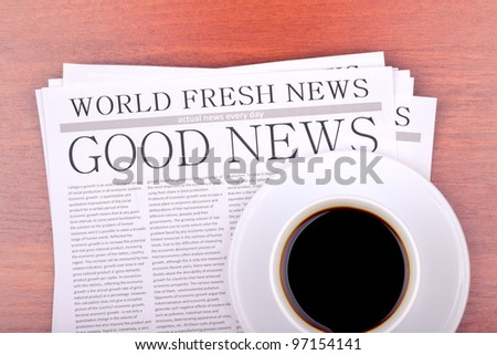 Newspaper GOOD NEWS and cup of coffee top view