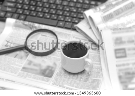 Newspaper, magnifier, cup of coffee and laptop. A pile of daily newspapers with news Headlines. Modern gadgets and old magazines.