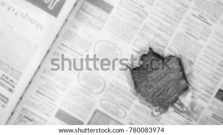 Newspaper page with hole in the middle. Daily paper with news, articles, headlines, photos and text is ripped. Old journal texture for background, blurred #780083974
