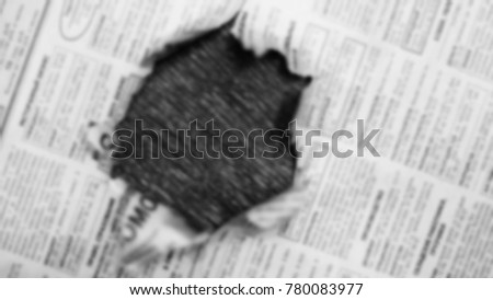 Newspaper page with hole in the middle. Daily paper with news, articles, headlines, photos and text is ripped. Old journal texture for background, blurred #780083977