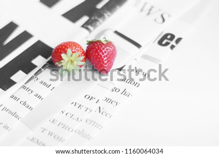 Newspaper pages and strawberries. Daily journals with headlines and articles and fresh fruits. Concept for juicy news                                  #1160064034