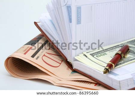 Newspaper, pen and notebook with cash on blue background