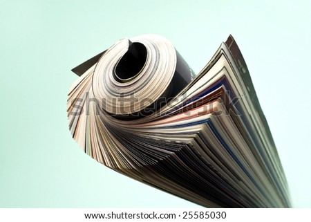 Newspaper rolled up green background isolate.