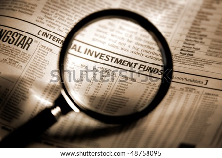 Newspaper section of the stock market index through the magnifying glass. Shallow depth of field