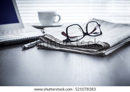 Newspaper with computer on table