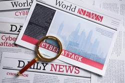 Newspaper with headline CYBER ATTACK and magnifying glass, top view