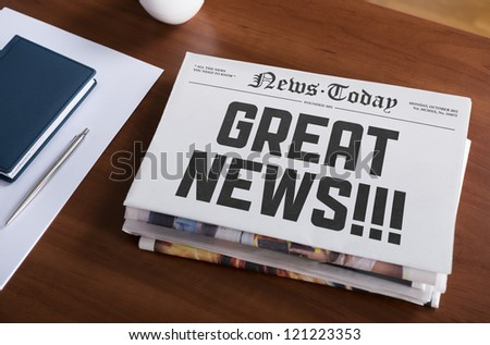 "Newspaper with hot topic ""Great news"" lying on office desk. - stock photo"