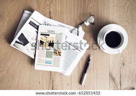 Photo of  Newspaper with tablet on wooden table