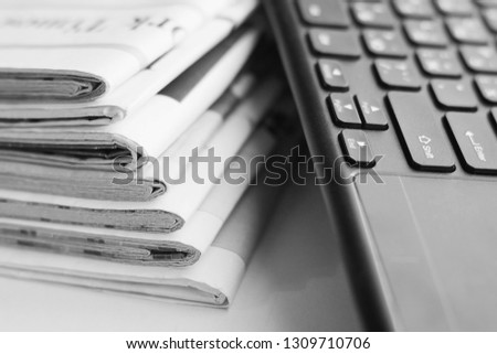 Newspapers and Computer Keyboard. Stack of Magazine Pages with Headlines and Articles and Electronic Devise. News and Journalism Concept