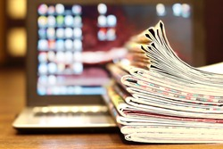 Newspapers and Computer. Magazines and Open Laptop. Tabloid Journals on Keypad of Notebook with Blurred Screen. Business Concept for News and Information, Different Data Sources