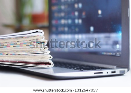 Newspapers and Laptop. Magazines and Journals and Computer. Paper Media and Electronic Device with Internet - Business News and Financial Information. Headlines, Articles and Digital Content #1312647059