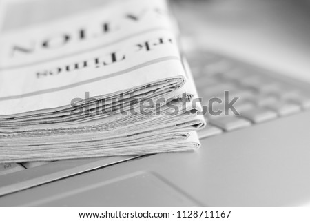 Newspapers and laptop. Pile of daily papers with news on the computer. Pages with headlines, articles folded and stacked on keypad of electronic device. Modern gadget and old journals, focus on paper  #1128711167