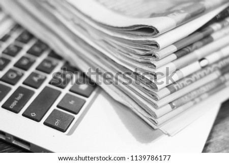Newspapers and laptop. Pile of daily papers with news on the computer. Pages with headlines, articles folded and stacked on keypad of electronic device. Modern gadget and old journals, focus on paper  #1139786177