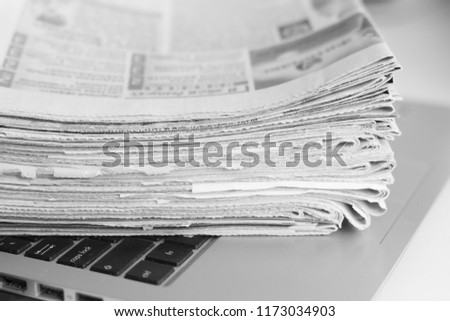 Newspapers and laptop. Pile of daily papers with news on the computer. Pages with headlines, articles folded and stacked on keypad of electronic device. Modern gadget and old journals, focus on paper  #1173034903