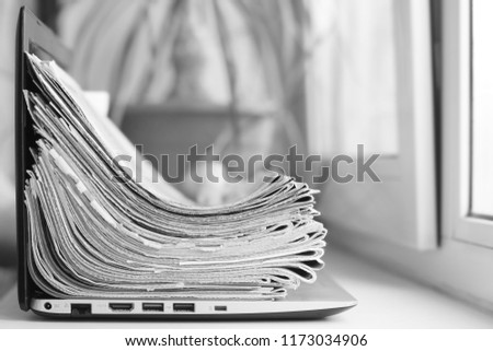 Newspapers and laptop. Pile of daily papers with news on the computer. Pages with headlines, articles folded and stacked on keypad of electronic device. Modern gadget and old journals, side view #1173034906
