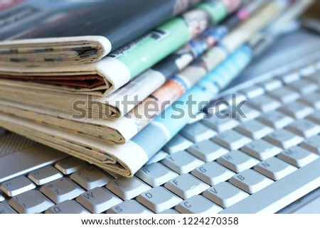 Newspapers and laptop. Pile of daily papers with news on the computer. Pages with headlines, articles folded and stacked on keypad of electronic device. Modern gadget and old journals, focus on paper  #1224270358