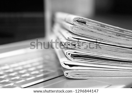 Newspapers and laptop. Pile of daily papers with news on the computer. Pages with headlines, articles folded and stacked on keypad of electronic device. Modern gadget and old journals, focus on paper  #1296844147