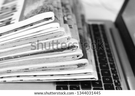 Newspapers and laptop. Pile of daily papers with news on the computer. Pages with headlines, articles folded and stacked on keypad of electronic device. Modern gadget and old journals, focus on paper  #1344031445