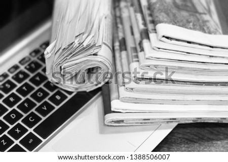 Newspapers and laptop. Pile of daily papers with news on the computer. Pages with headlines, articles folded and stacked on keypad of electronic device. Modern gadget and old journals, focus on paper