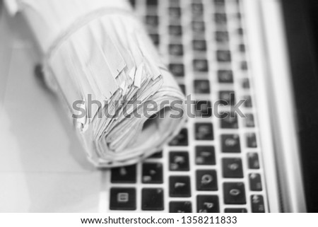 Newspapers and laptop. Rolled daily papers with news on the computer. Pages with headlines, articles on keypad of electronic device. Modern gadget and old journals, focus on paper