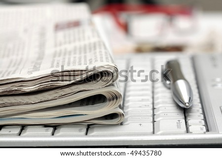 Newspapers and pen on notebook keyboard