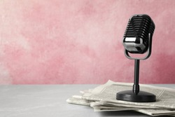 Newspapers and vintage microphone on table, space for text. Journalist's work