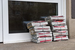 Newspapers distributed stacked on a front door
