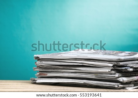 Newspapers folded and stacked on wooden board