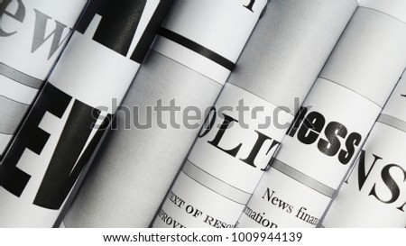 Newspapers, folded and stacked. Side view of headlines and articles on daily papers witn news #1009944139
