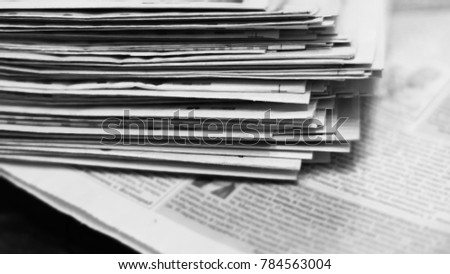 Newspapers for background. Old English daily papers with news on the table. Pages with headlines and articles folded and stacked, grange style. Blurred retro texture.                              #784563004